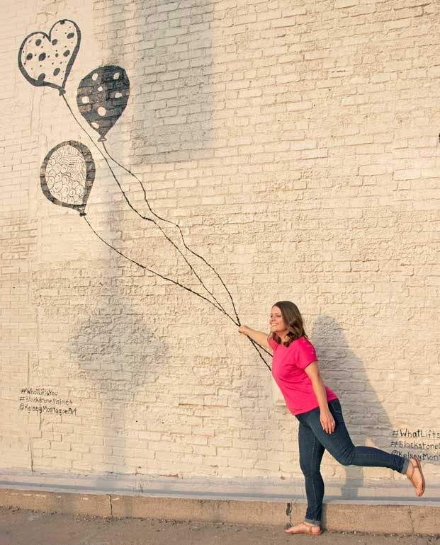 holding balloons at the Kelsey Montague mural in Omaha