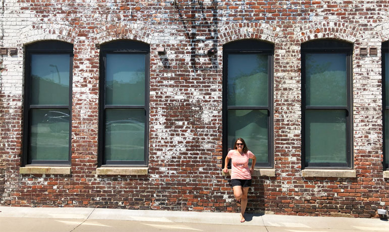 Nikki standing in front of a brick wall with windows