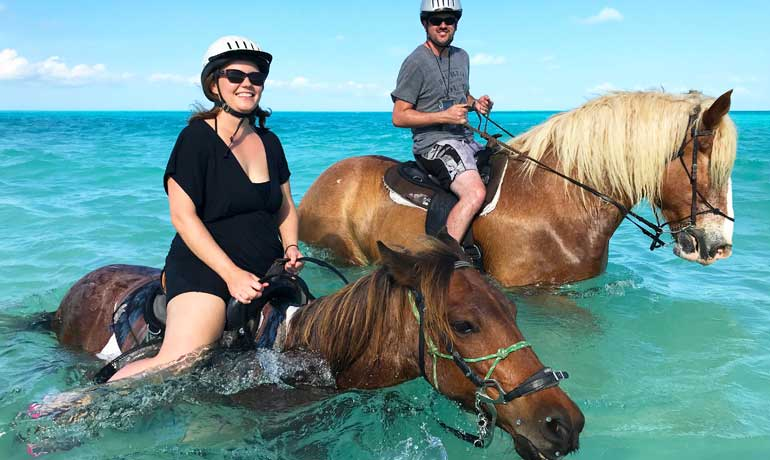 turks and caicos excursions horseback riding travel couple on horses in ocean