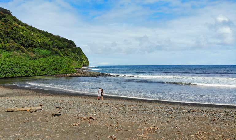 couple on an empty beach on the road to hana with hillside in background