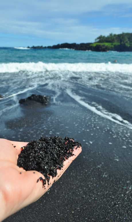 hand holding black sand with beach in background
