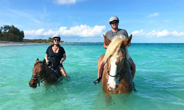 horseback riding in providenciales on long bay beach two riders on horses in ocean