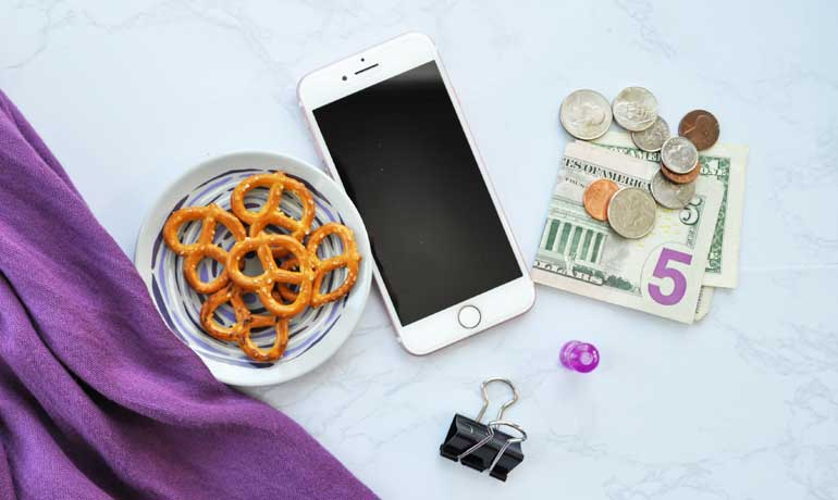 importance of saving money items laying on counter money phone pretzels