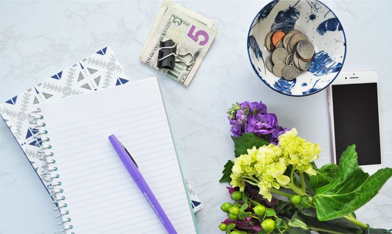 is saving money important money lyiing on desk with flowers and phone