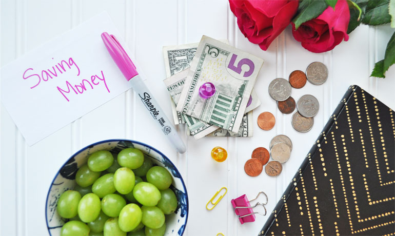 importance of savings money items on a white board roses notebook grapes