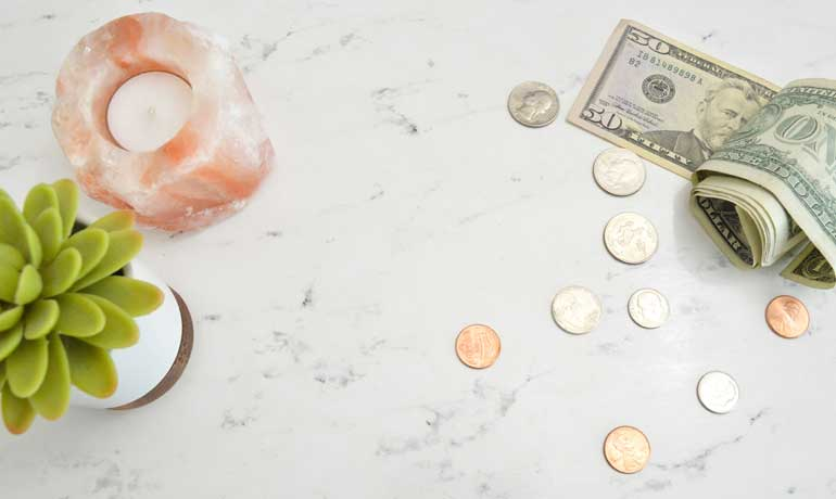 why saving money is important money on countertop with candle and succulent