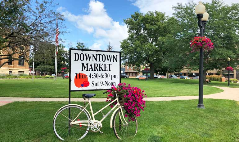 downtown market estherville sign with bike and town square with flowers