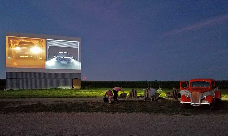 old fashioned drive in movie with classic car and screen