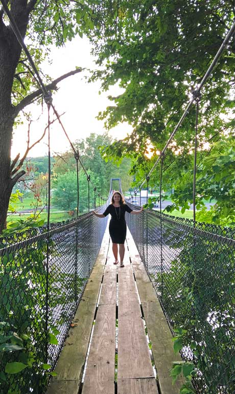 wooden swinging bridge - shesavesshetravels nikki standing on bridge