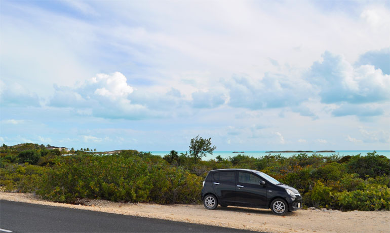 rent a car in turks and caicos car along the road with beach in background