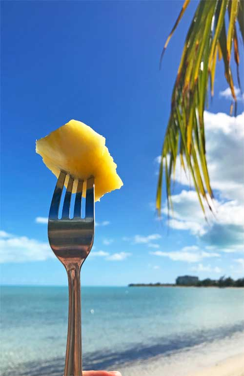 eating for cheap in the caribbean - pineapple on fork at the beach