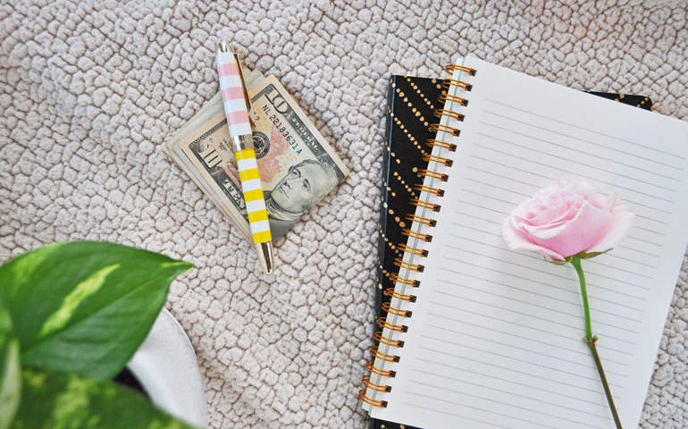 money with notebook and rose