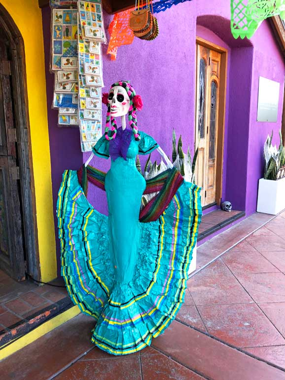 colorful Dia de los Muertos mannequin with buildings