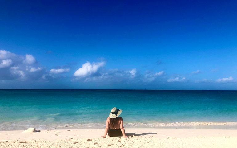 woman sitting on divi beach, aruba